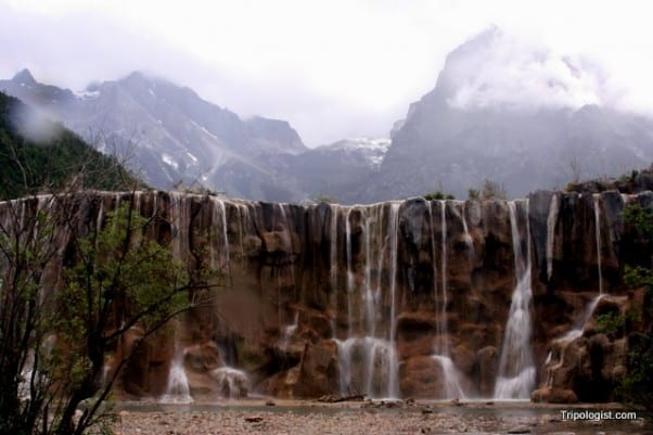 A waterfall on the White River with Jade Dragon Snow Mountain in the background.