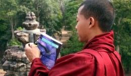 A Buddhist Monk carries his Cambodia Lonely Planet while visiting Angkor Thom temple in Siem Reap, Cambodia.