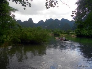 My wife and our 2 bikes being paddled across the Yulong River on a homemade bamboo raft.