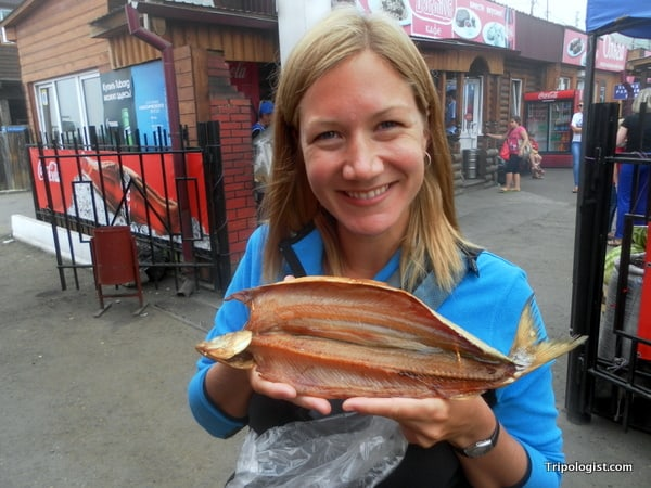 My wife, Julie, holding our smoked omul in Listvyanka, Russia.