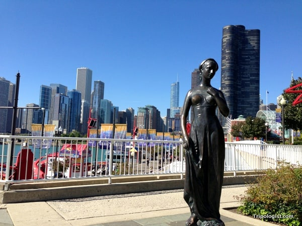 A statue of Juliet with the Chicago skyline in the background.