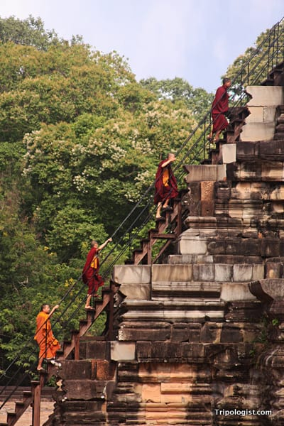Four Buddhist monks climb a temple at Angkor Thom in Siem Reap, Cambodia.